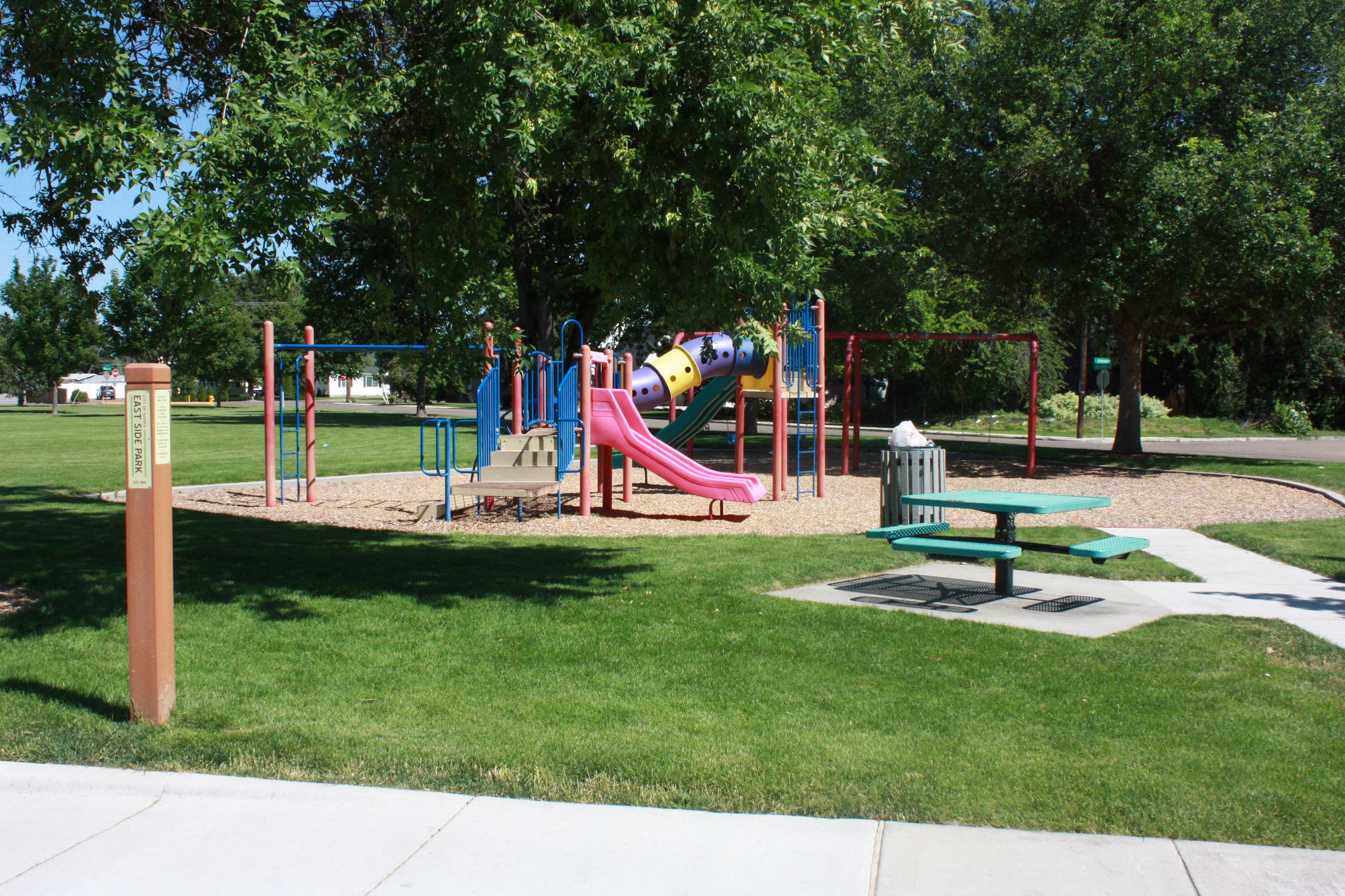 Multicolored play structure with small green picnic table on the side